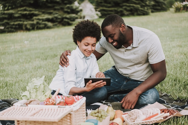 Afro son and father looking on tablet on picnic