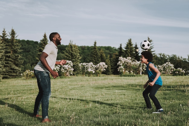 Afro son and father play together in ball on nature