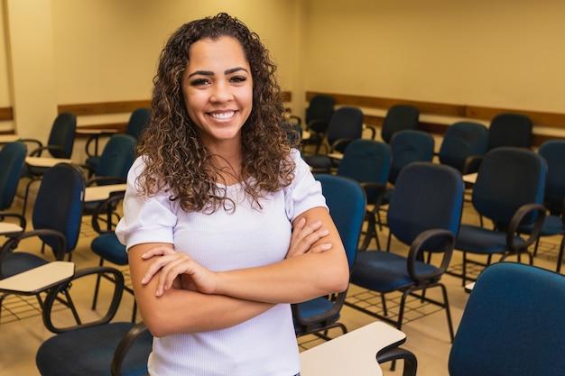 カメラの笑顔を見て腕を組んで教室のアフロ学生。バックグラウンドで教室を持つ若い学生。