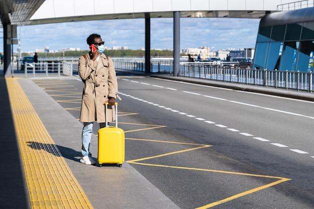 アフロ旅行者の男性が空港ターミナルに立ち、携帯電話と待機中のタクシーを呼び、フェイスマスクを着用します。
