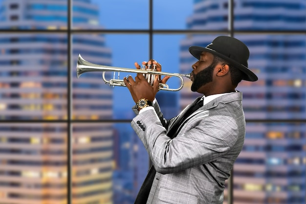 Afro trumpeter in black hat.