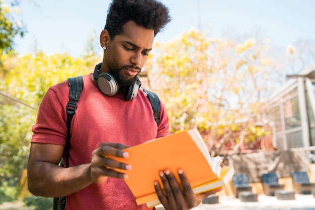 Afro university student studying and reading his book