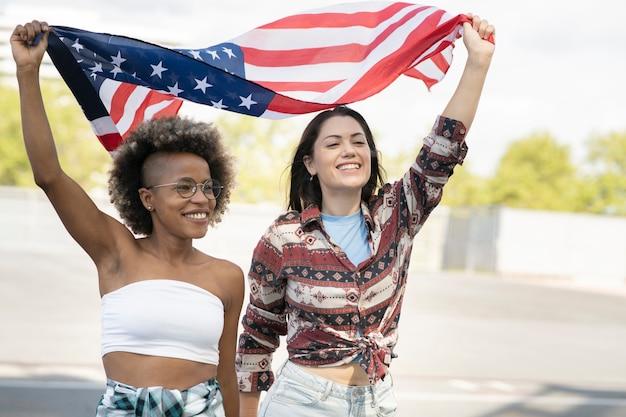 アフロの女性と白人の女性は非常に幸せに米国旗を保持しています