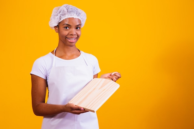 Afro woman in apron holding a meat board with space for text.