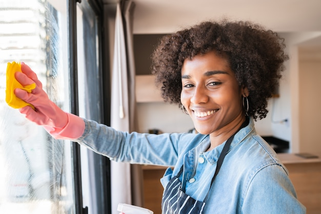 自宅でぼろきれで窓拭きアフロ女性