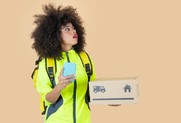 パッケージ、バックパック、スマートフォンを持つアフロ女性分娩の女の子