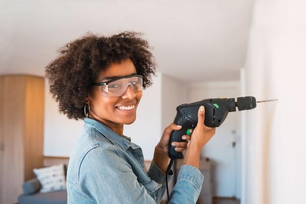 電気ドリルでアフロ女性掘削壁