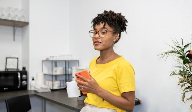 アフロの女性がオフィスのキッチンでコーヒーを飲む