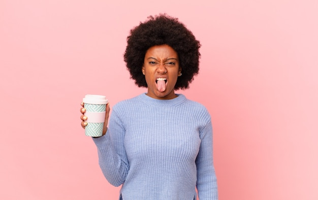 Afro woman feeling disgusted and irritated, sticking tongue out, disliking something nasty and yucky. coffee concept