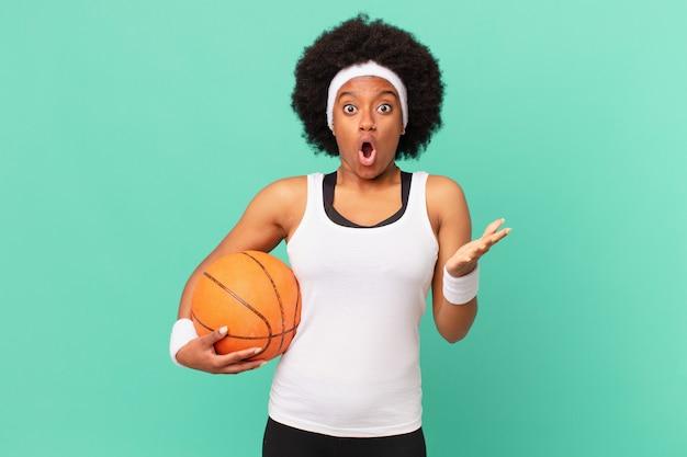 Афро-женщина чувствует себя чрезвычайно потрясенной и удивленной, встревоженной и панической, с напряженным и испуганным взглядом. баскетбольная концепция