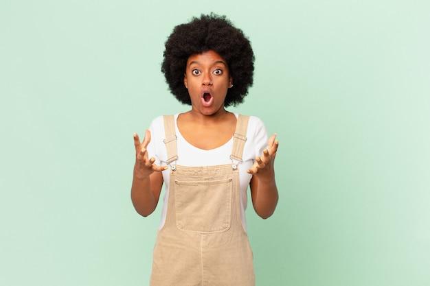 Афро-женщина чувствует себя чрезвычайно шокированной и удивленной, встревоженной и панической, с напряженным и испуганным взглядом шеф-повара