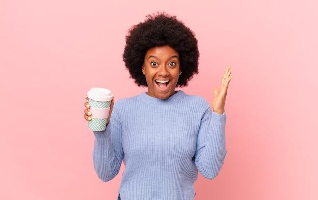 信じられないほどの何かに幸せ、興奮、驚き、ショックを受け、笑顔で驚いたアフロの女性。コーヒーのコンセプト