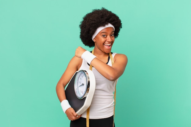 Afro woman feeling happy, positive and successful, motivated when facing a challenge or celebrating good results diet concept
