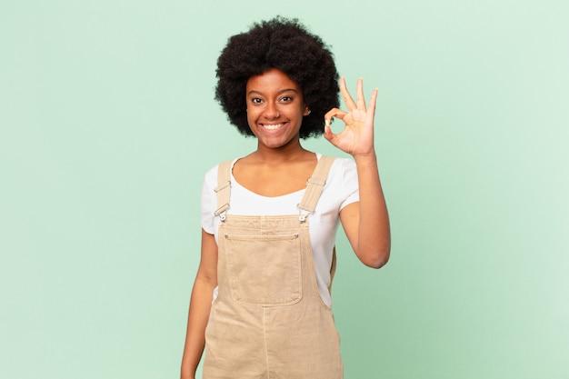 Афро-женщина чувствует себя счастливой, расслабленной и удовлетворенной, демонстрирует одобрение с нормальным жестом, улыбаясь концепции шеф-повара