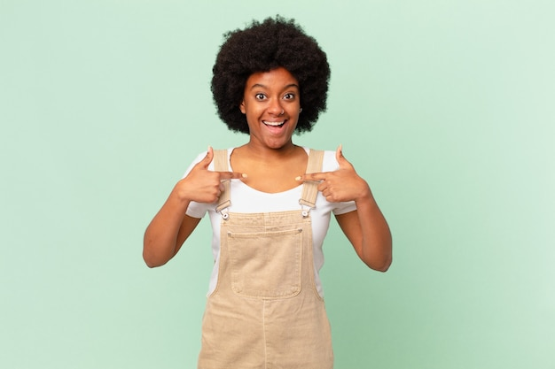 Афро-женщина чувствует себя счастливой, удивленной и гордой, указывая на себя взволнованным, изумленным взглядом шеф-повара