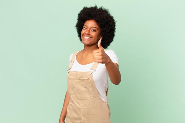 Афро-женщина чувствует себя гордой, беззаботной, уверенной и счастливой, позитивно улыбается с большими пальцами руки вверх концепция шеф-повара
