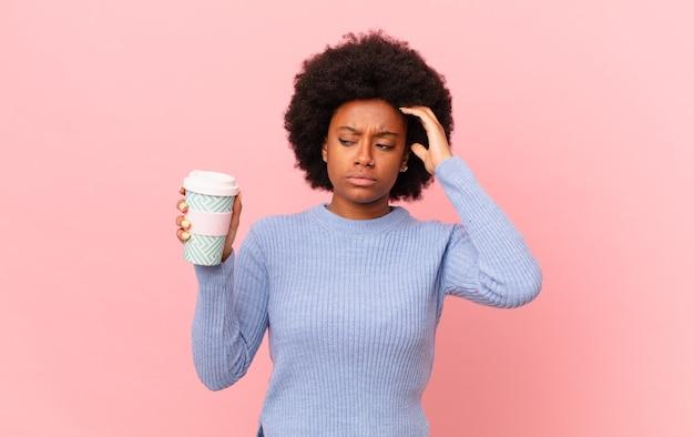 アフロの女性は戸惑い、混乱し、頭を掻き、横を向いていると感じています。コーヒーのコンセプト