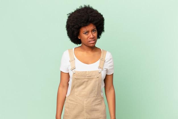 Афро-женщина чувствует себя озадаченной и сбитой с толку, с тупым, ошеломленным выражением лица смотрит на что-то неожиданное понятие шеф-повара