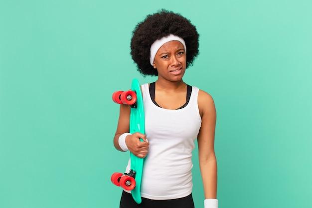 戸惑い混乱しているアフロの女性は、思いがけない何かを見ている愚かな、唖然とした表情で。スケートボードのコンセプト