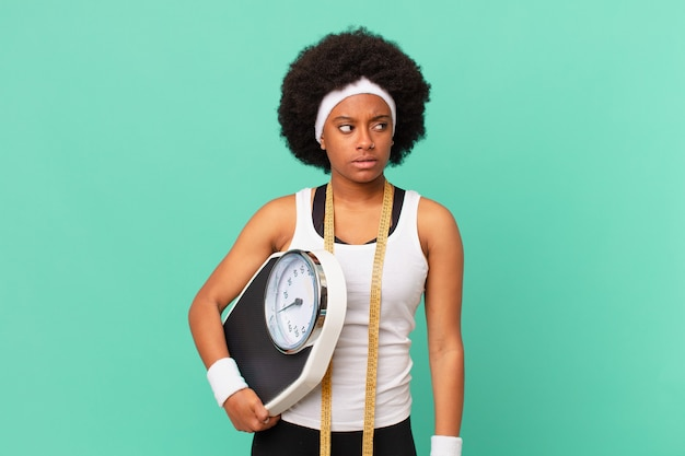 Afro woman feeling sad, upset or angry and looking to the side with a negative attitude, frowning in disagreement diet concept