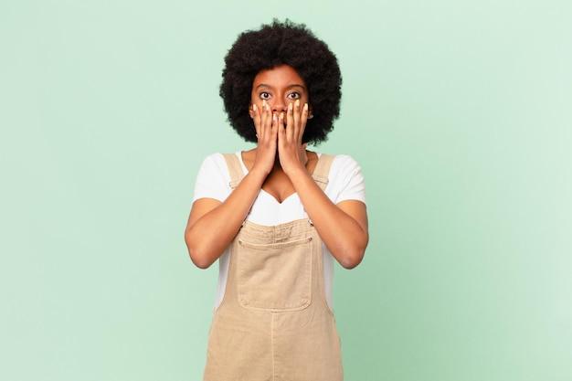 Афро-женщина чувствует себя потрясенной и напуганной, выглядит испуганной с открытым ртом и руками на щеках, концепция шеф-повара