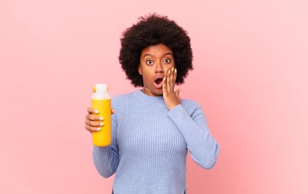 Афро-женщина чувствует себя потрясенной и испуганной, выглядит испуганной с открытым ртом и руками по щекам. концепция смузи