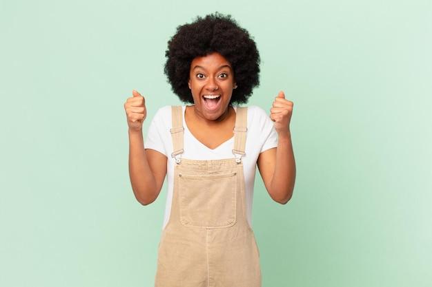 Афро-женщина чувствует себя потрясенной, взволнованной и счастливой, смеется и празднует успех, говоря
