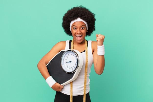 アフロの女性はショックを受け、興奮し、幸せになり、笑い、成功を祝い、すごい!ダイエットコンセプト