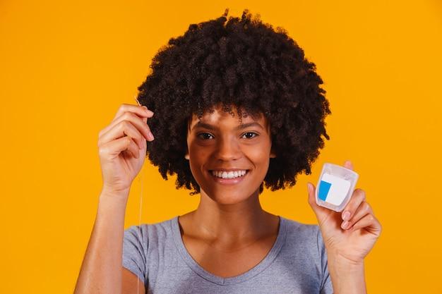 アフロの女性が歯をフロスします。お口の健康の概念