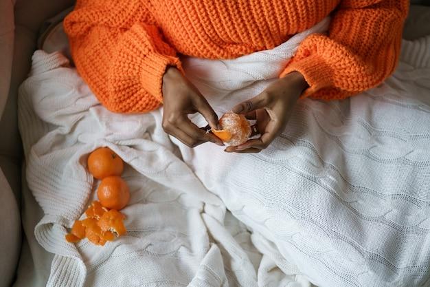 Афро-женщина руками чистит спелый сладкий мандарин, носить оранжевый свитер, лежа в постели под пледом