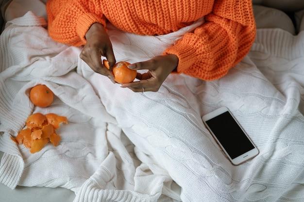 Афро-женщина руками чистит спелый сладкий мандарин, носить оранжевый свитер, лежа в постели под белым вязанным пледом. зимние фрукты, концепция рождества.