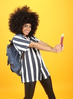 Афро-женщина счастлива, потому что у нее есть паспорт для путешествий
