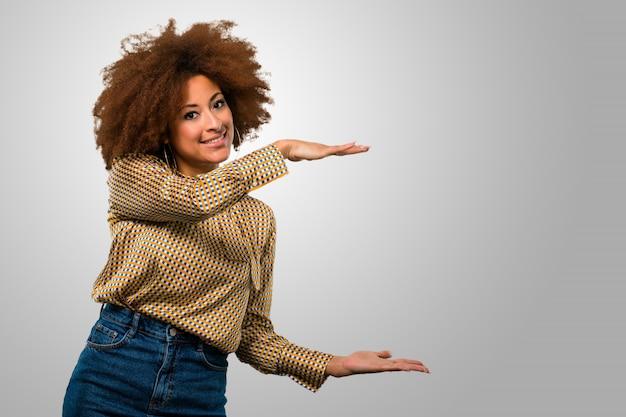 Afro woman holding something
