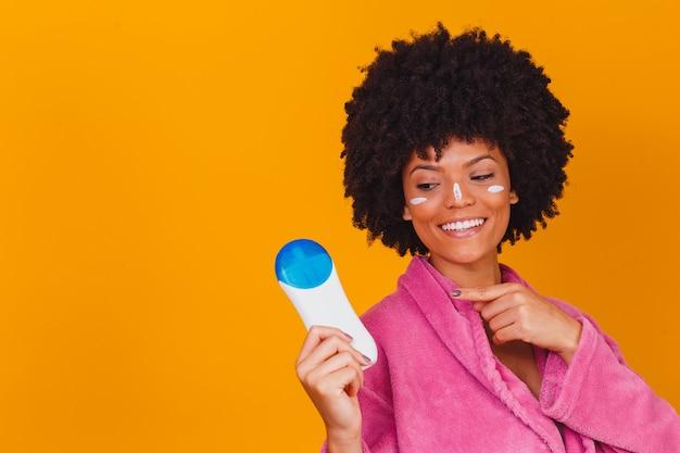 노란색 배경에서 손에 자외선 차단제를 들고 아프리카 여자. 여름 컨셉