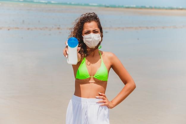 ビーチで日焼け止めのボトルを手に持っているビキニとマスクのアフロ女性。