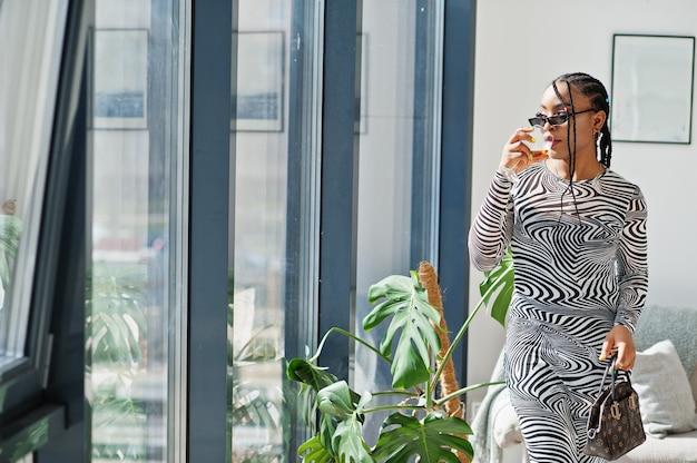 屋内でポーズをとったゼブラドレスのアフロ女性