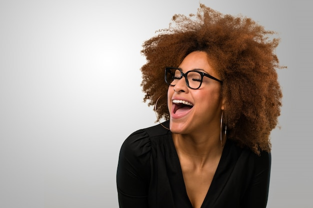 Afro woman laughing happy wearing glasses