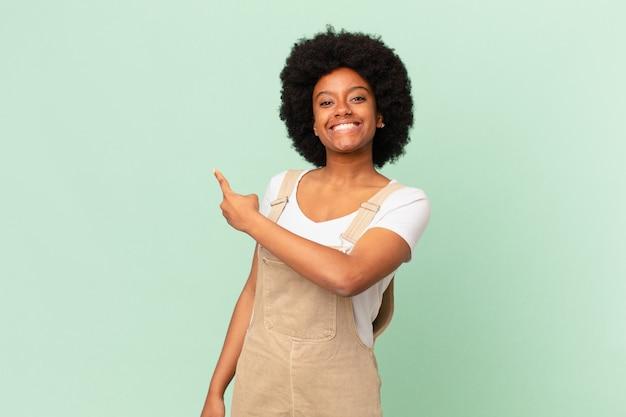 Афро-женщина выглядит взволнованной и удивленной, указывая в сторону и вверх, чтобы скопировать концепцию космического шеф-повара