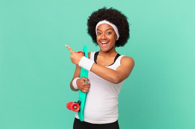Афро-женщина выглядит взволнованной и удивленной, указывая в сторону и вверх, чтобы скопировать пространство. концепция скейтборда