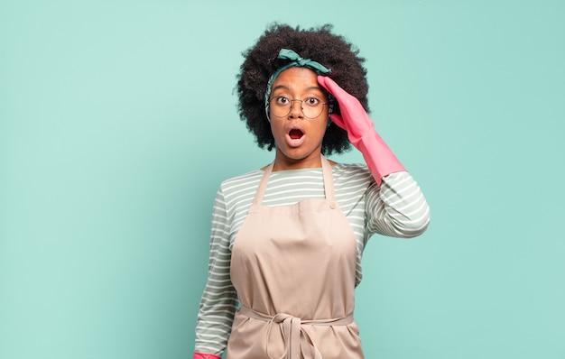 幸せに見え、驚き、驚き、笑顔で、驚くべき信じられないほどの良いニュースを実現しているアフロの女性。ハウスキーピングの概念。