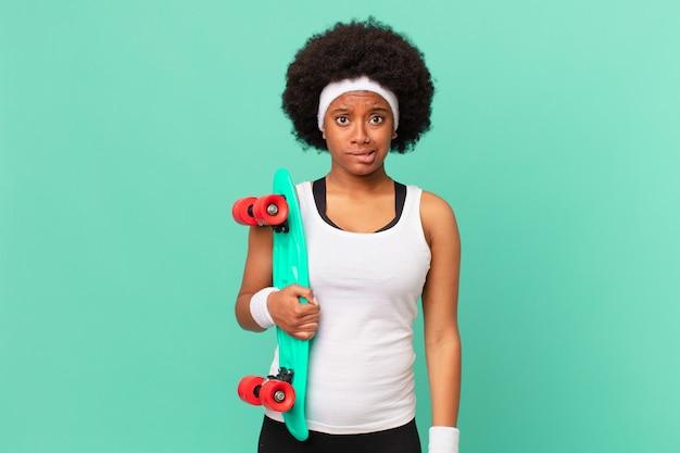 困惑して混乱しているように見えるアフロの女性は、神経質なジェスチャーで唇を噛み、問題の答えを知りません。スケートボードのコンセプト