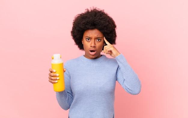 驚いた、口を開いた、ショックを受けた、新しい考え、アイデア、または概念を実現しているアフロの女性。スムージーコンセプト