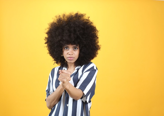 Afro woman, makes boxing gesture, casual clothes, yellow background