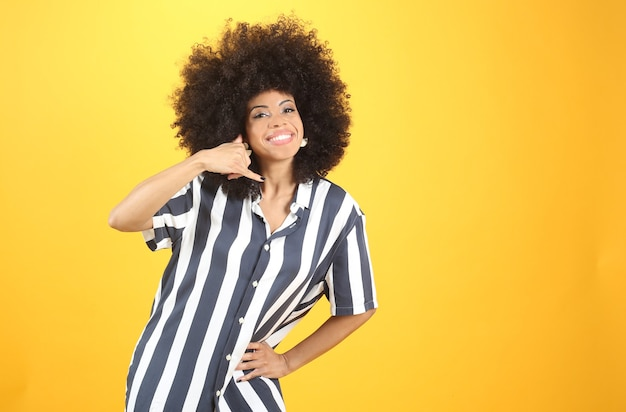 Afro woman, makes phone call gesture with hand, casual clothes, on yellow background