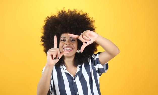 Афро-женщина делает фото жест руками