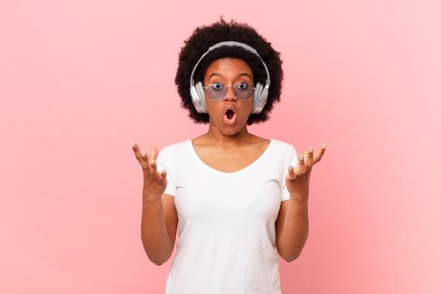 アフロの女性は口を開けて驚いて、ショックを受けて、信じられないほどの驚きに驚いた。音楽のコンセプト