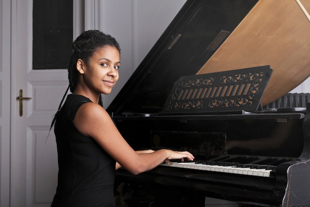 Afro woman playing on a piano