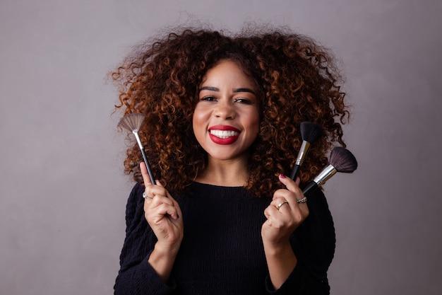 Afro woman professional makeup artist holding makeup brushes.