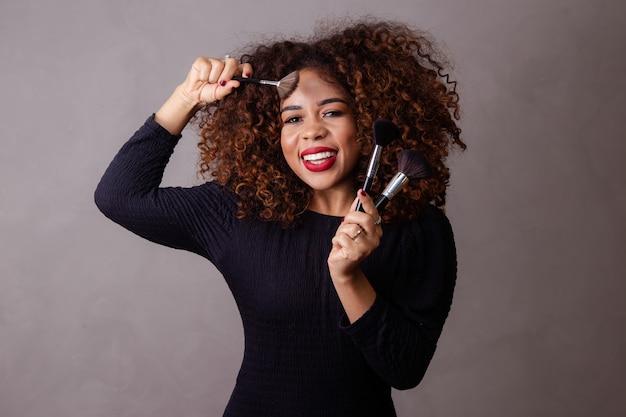 メイクブラシを保持しているアフロ女性プロのメイクアップアーティスト。