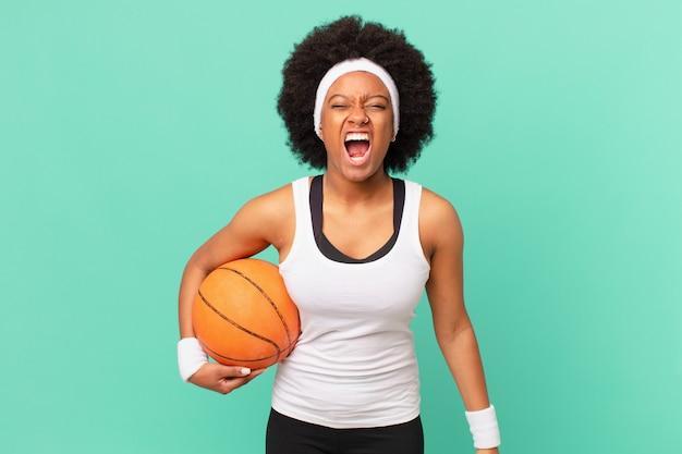아프로 여성은 매우 화나고, 좌절하고, 화를 내거나 짜증을 내며 공격적으로 소리를 지르며 아니오를 비명을 지릅니다. 농구 개념